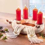 Czerwone świece wigilijne zdobione w białym wieńcu.